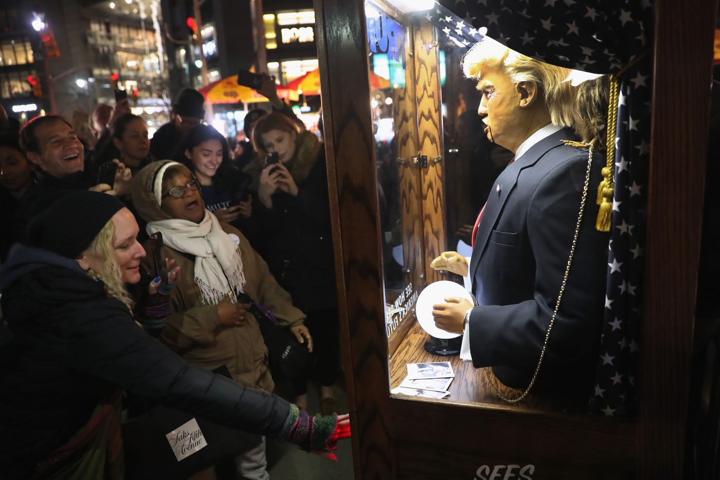 """People listen to a recording of a Trump impersonation outside a """"We Stand United"""" anti-Trump rally on January 19, 2017 in New York City. Thousands of people gathered outside the Trump International Hotel in Manhattan to protest on the eve of Donald Trump's inauguration as the 45th President of the United States."""