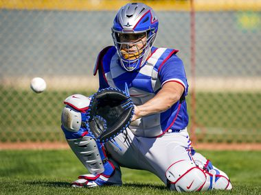 Texas Rangers catcher Robinson Chirinos  participates in a drill during a spring training workout at the team's training facility on Saturday, Feb. 15, 2020, in Surprise, Ariz.