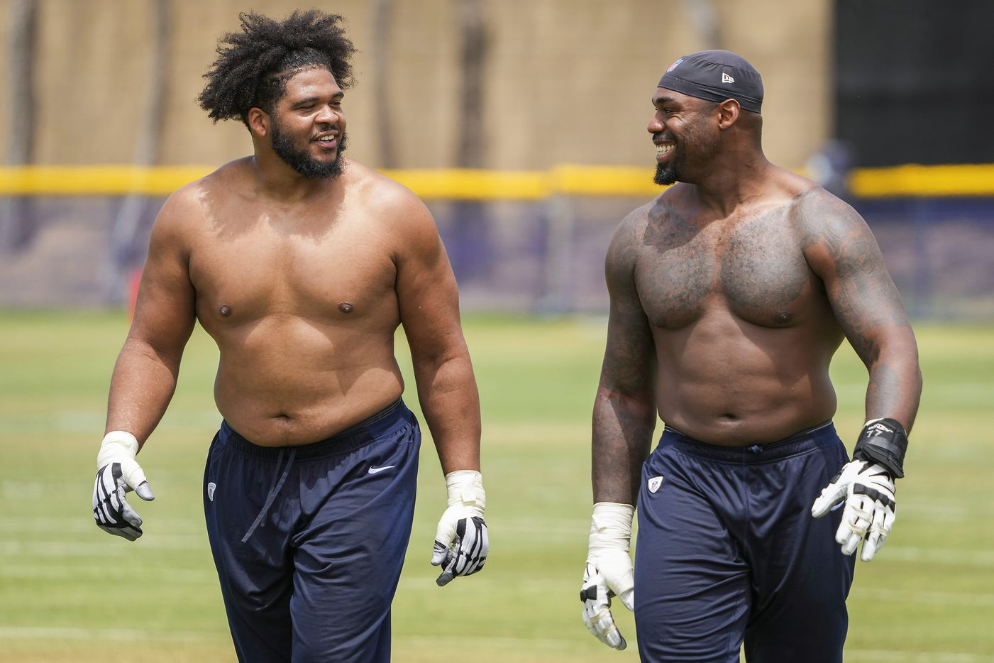 Dallas Cowboys tackle La'el Collins (left) laughs with tackle Tyron Smith as they leave the field following a practice at training camp on Saturday, July 24, 2021, in Oxnard, Calif.
