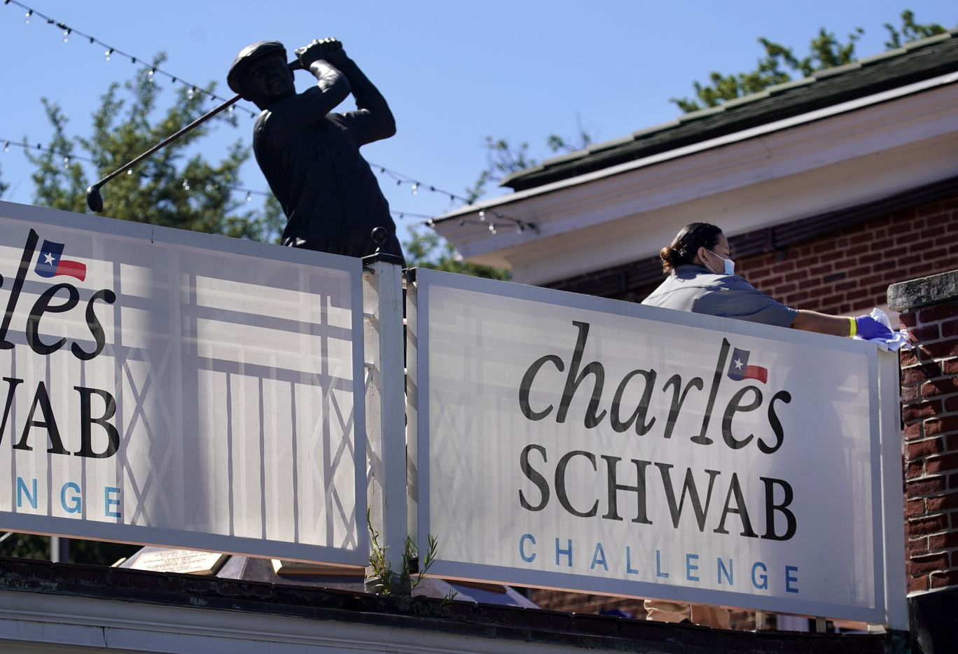 A woman cleans the railings near the Ben Hogan statue during the opening round of the Charles Schwab Challenge at the Colonial Country Club in Fort Worth, Thursday, June 11, 2020.  The Challenge is the first tour event since the COVID-19 pandemic began. (Tom Fox/The Dallas Morning News)
