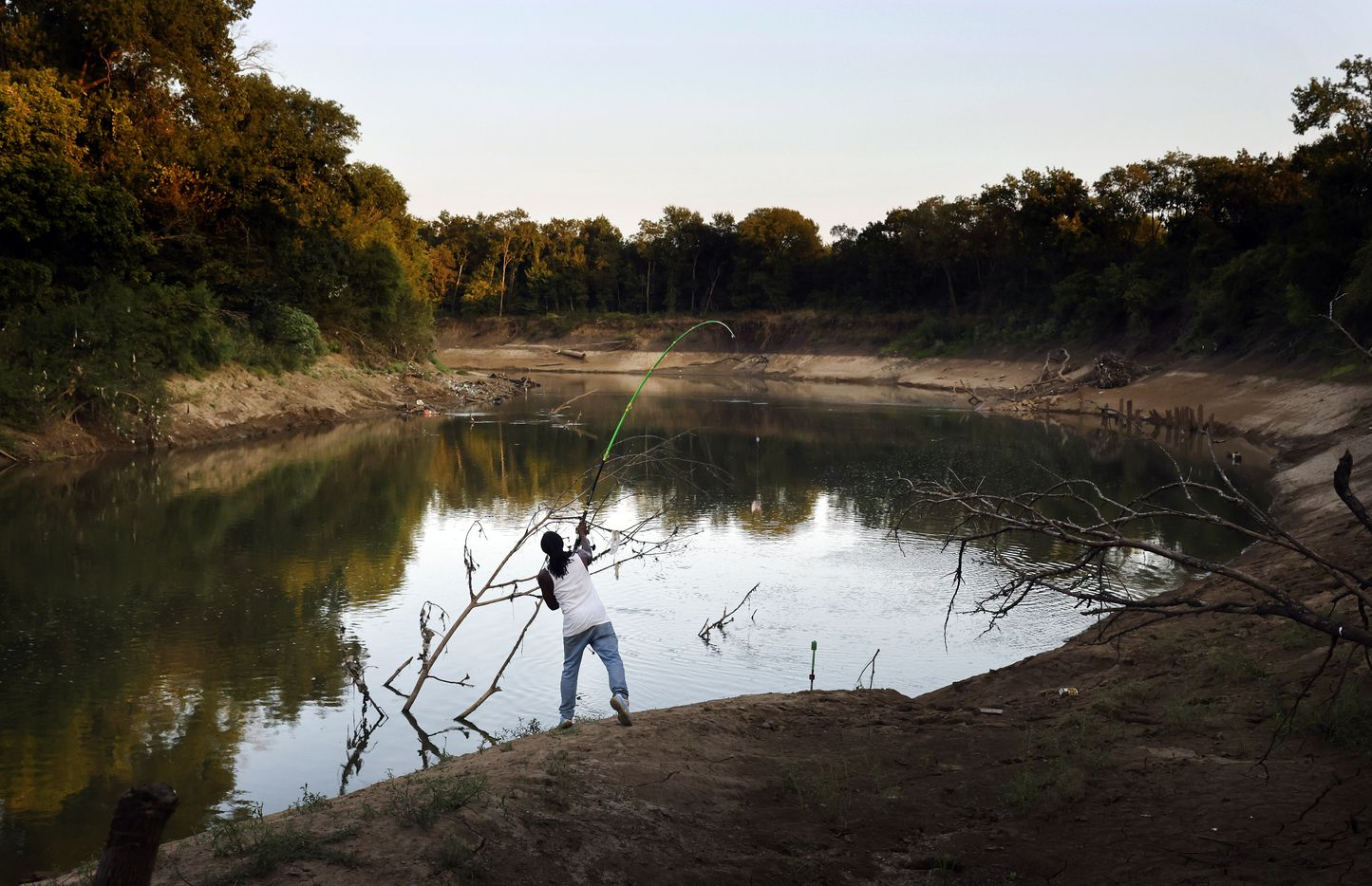 Odell Allen cast his line in hopes of reeling in an alligator gar on the Trinity River near the Great Trinity Forest Way bridge in Dallas, Wednesday, September 1, 2021.  Allen's viral videos of him catching 6-7 foot gars have made Dallas a popular spot for anglers all over the world who want to hook a gar. It has also led to overfishing of the native species, TPWD says. Texas Parks and Wildlife Department is adding new regulations to limit how many gar each angler can harvest in a year. Allen catches and releases his gar. (Tom Fox/The Dallas Morning News)