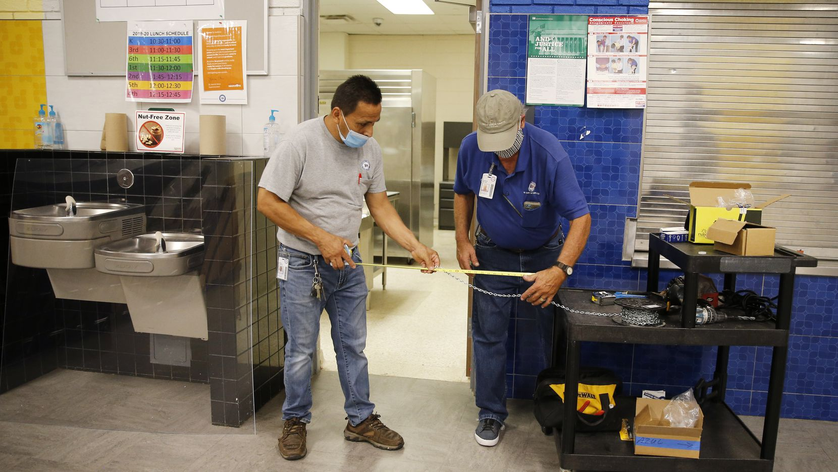 RISD maintenance workers Rogelio Ponciano (left) and Charles De Long measure chain to cut for installing a germ barrier inside the cafeteria at Prestonwood Elementary School in Dallas, on Thursday, July 16, 2020. (Vernon Bryant/The Dallas Morning News)