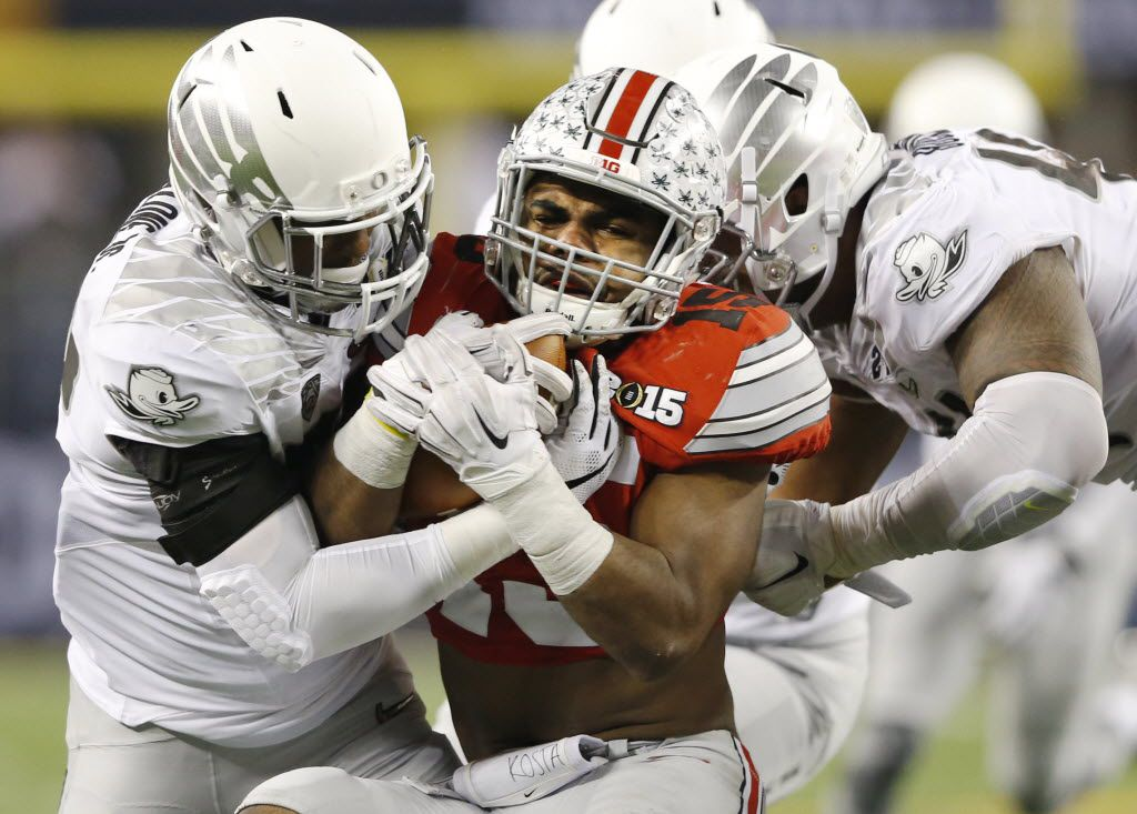 Oregon Ducks linebacker Derrick Malone (22) and Oregon Ducks defensive lineman DeForest Buckner (44) tackle Ohio State Buckeyes running back Ezekiel Elliott (15) on a run attempt during the first half of the College Football Playoff National Championship at AT&T Stadium in Arlington, on Monday, January 12, 2015. (Vernon Bryant/The Dallas Morning News)