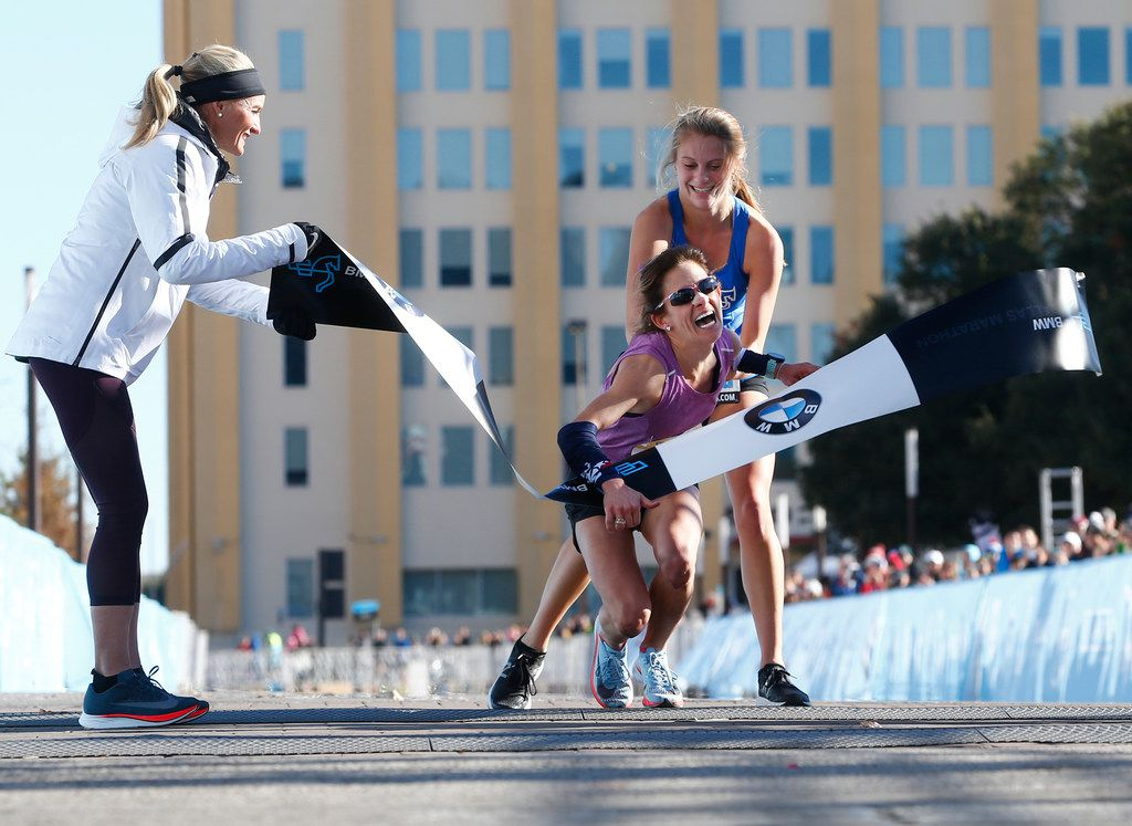 Shalane Flanagan, four-time Olympian, (left) watches as Chandler Self, winner of the full marathon is helped by relay runner Ariana Luterman, 17, from Greenhill School, at the finish line during the BMW Dallas Marathon in downtown Dallas on Dec. 10, 2017.  (Nathan Hunsinger/The Dallas Morning News)