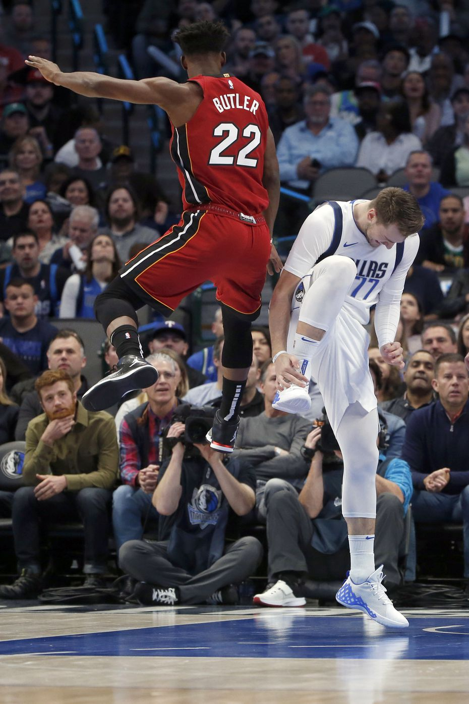 Dallas Mavericks forward Luka Doncic (77) reacts after injuring himself as Miami Heat forward Jimmy Butler (22) defends him during the first half of an NBA basketball game in Dallas, Saturday, Dec 14, 2019. (AP Photo/Michael Ainsworth)
