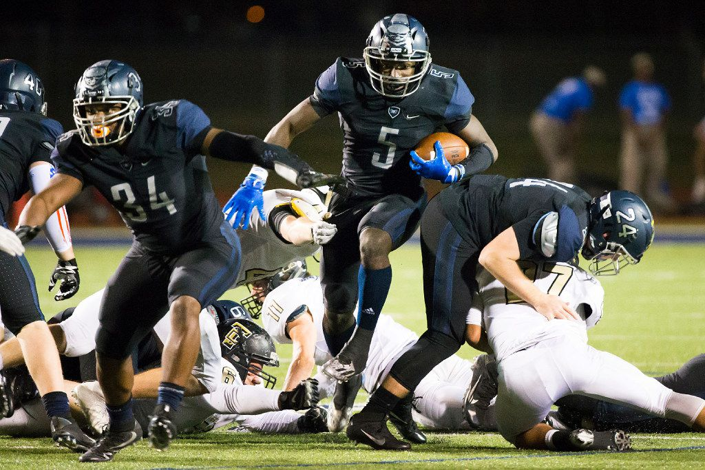 Wylie East quarterback  Eno Benjamin (5) gets blocks from Jordan Jeffrey (34) and Michael Messer (24) as he picks up a first down during the second half of a UIL area round playoff football game against The Colony at Ron Poe Stadium on Thursday, Nov. 17, 2016, in McKinney.  Wylie East won the game 56-28. (Smiley N. Pool/The Dallas Morning News)