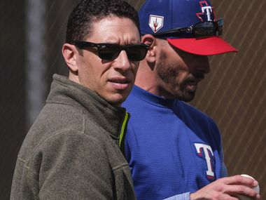 Texas Rangers general manager Jon Daniels (left) and manager Chris Woodward watch batting practice during the first full squad spring training workout at the team's training facility on Monday, Feb. 18, 2019, in Surprise, Ariz..