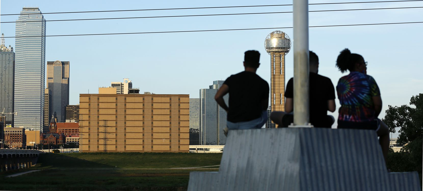 People at the Trinity Overlook Park watch as the sun sets on downtown Dallas and the former Jesse R. Dawson State Jail (center) at 106 West Commerce St.