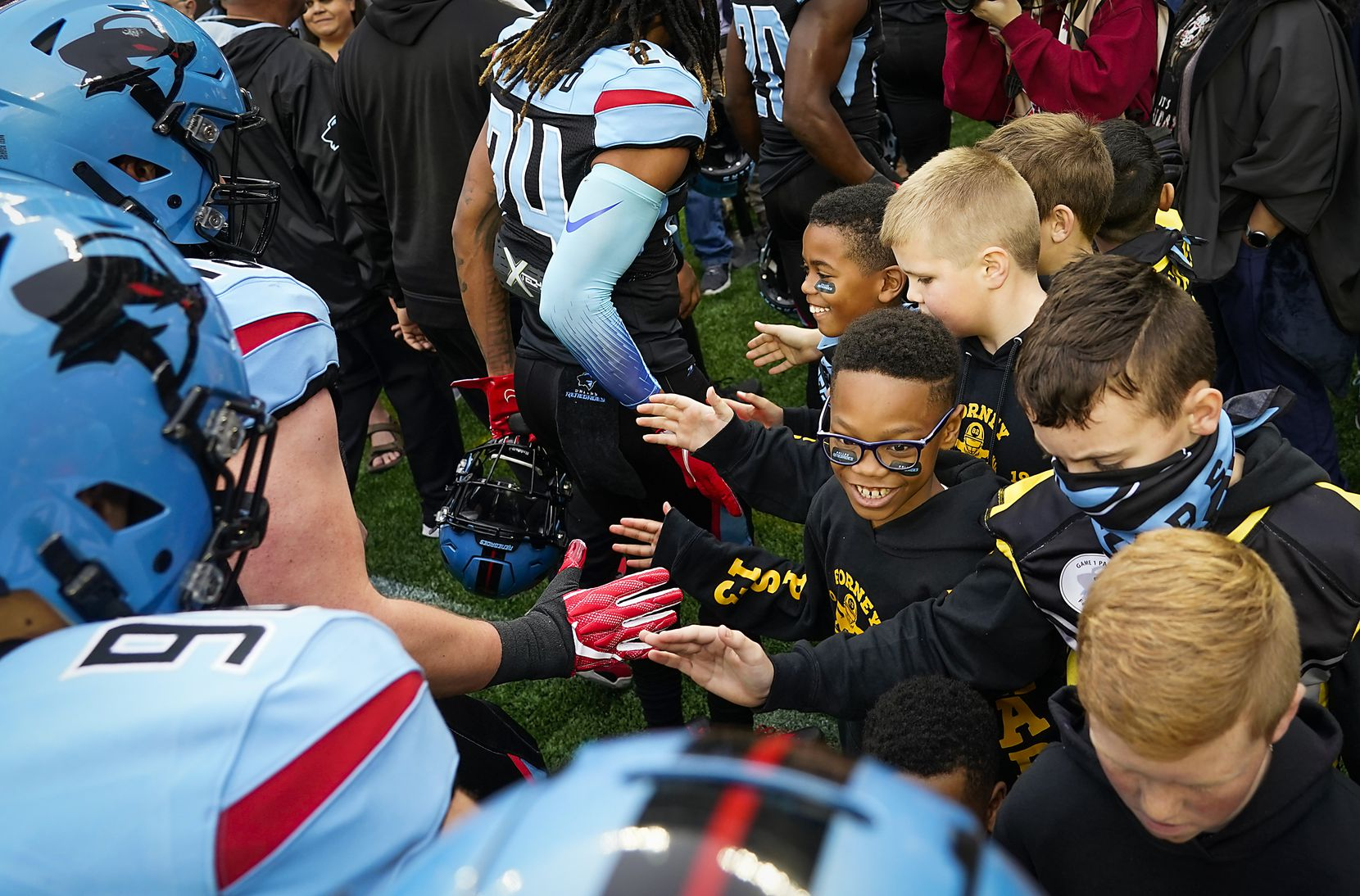 Dallas Renegades players high five members of the Forney Jackrabbits youth football team before an XFL football game against the St. Louis Battlehawks at Globe Life Park on Sunday, Feb. 9, 2020, in Arlington.