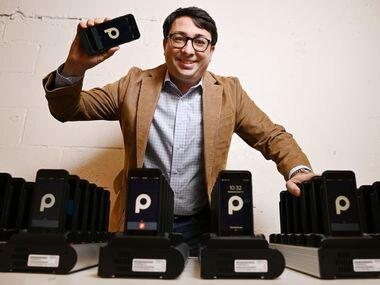 George Baker, founder, chairman and CEO of ParkHub, holds a point-of-sale device near a group of scanners at the company's offices in Dallas. The device can be used to sell or grant access into a parking or camping site.