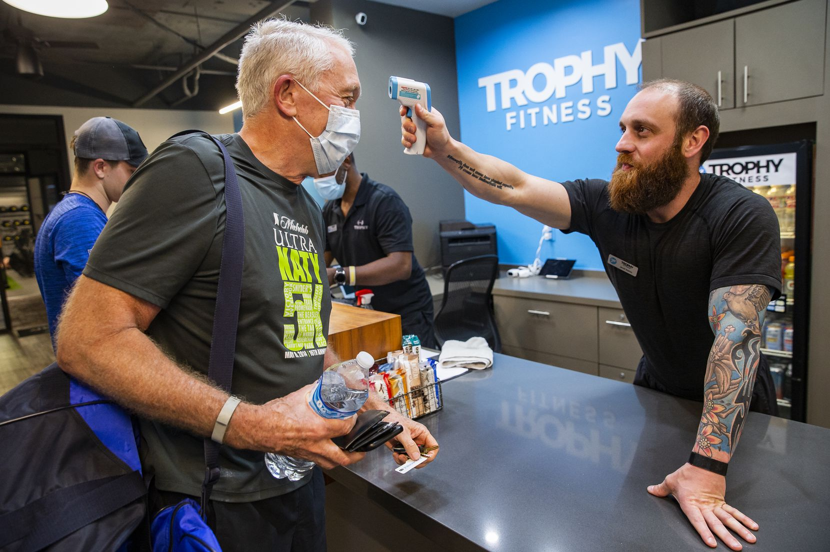 Client Durward Watson of Oak Lawn (left) has his temperature taken by a Trophy Fitness employee before being allowed to work out in the Uptown gym on May 18, 2020 in Dallas.
