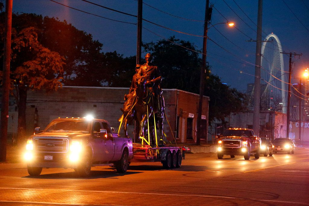 The Robert E. Lee statue is given a police escort after its removal from a public park in Dallas, Thursday, Sept. 14, 2017. In an unannounced move, a large crane was brought through the city by a police escort to Lee Park, where it lifted the large statue from its pedestal late Thursday afternoon.