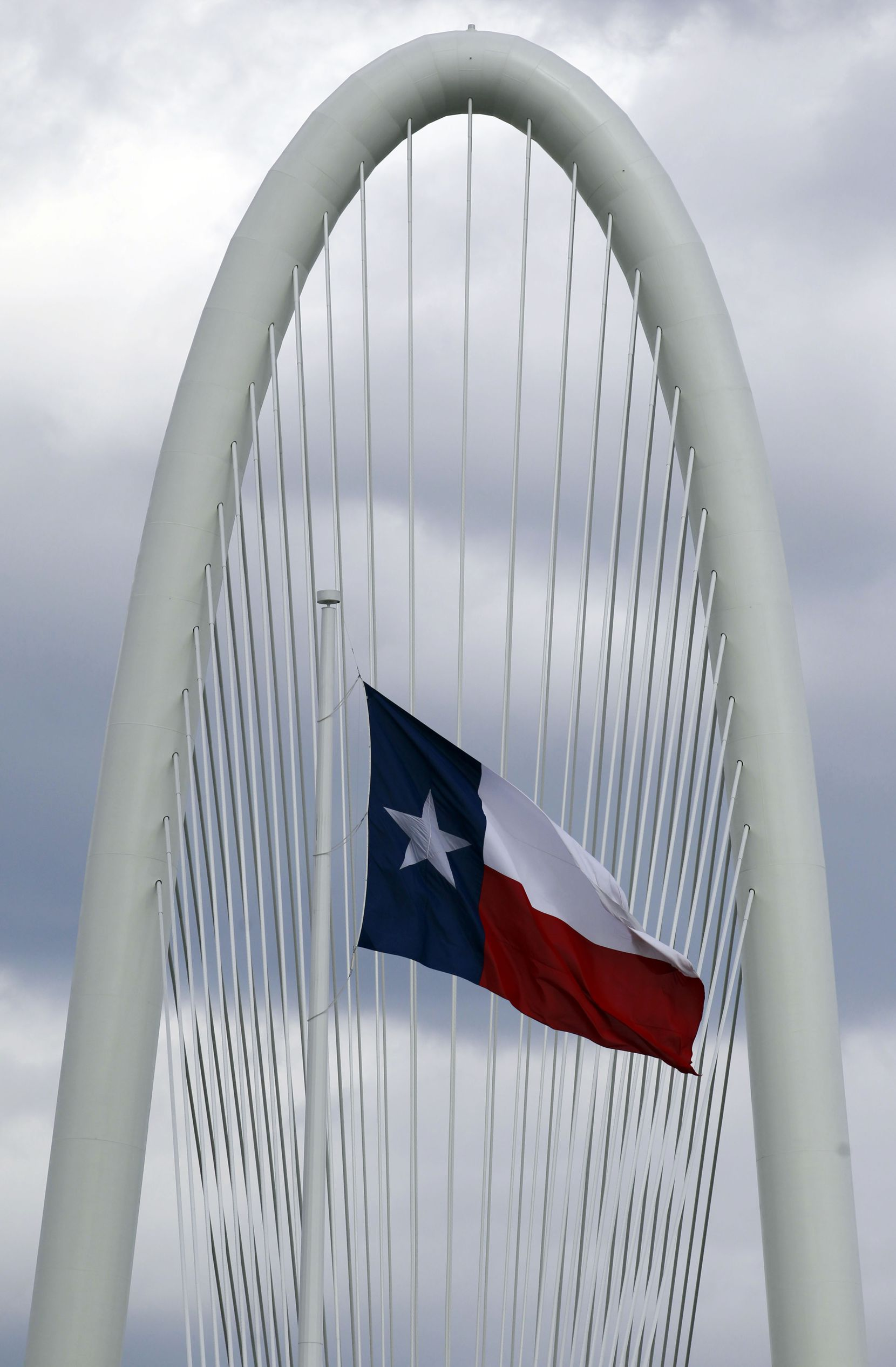 The Texas flag flutters near the Margaret Hunt Hill Bridge.