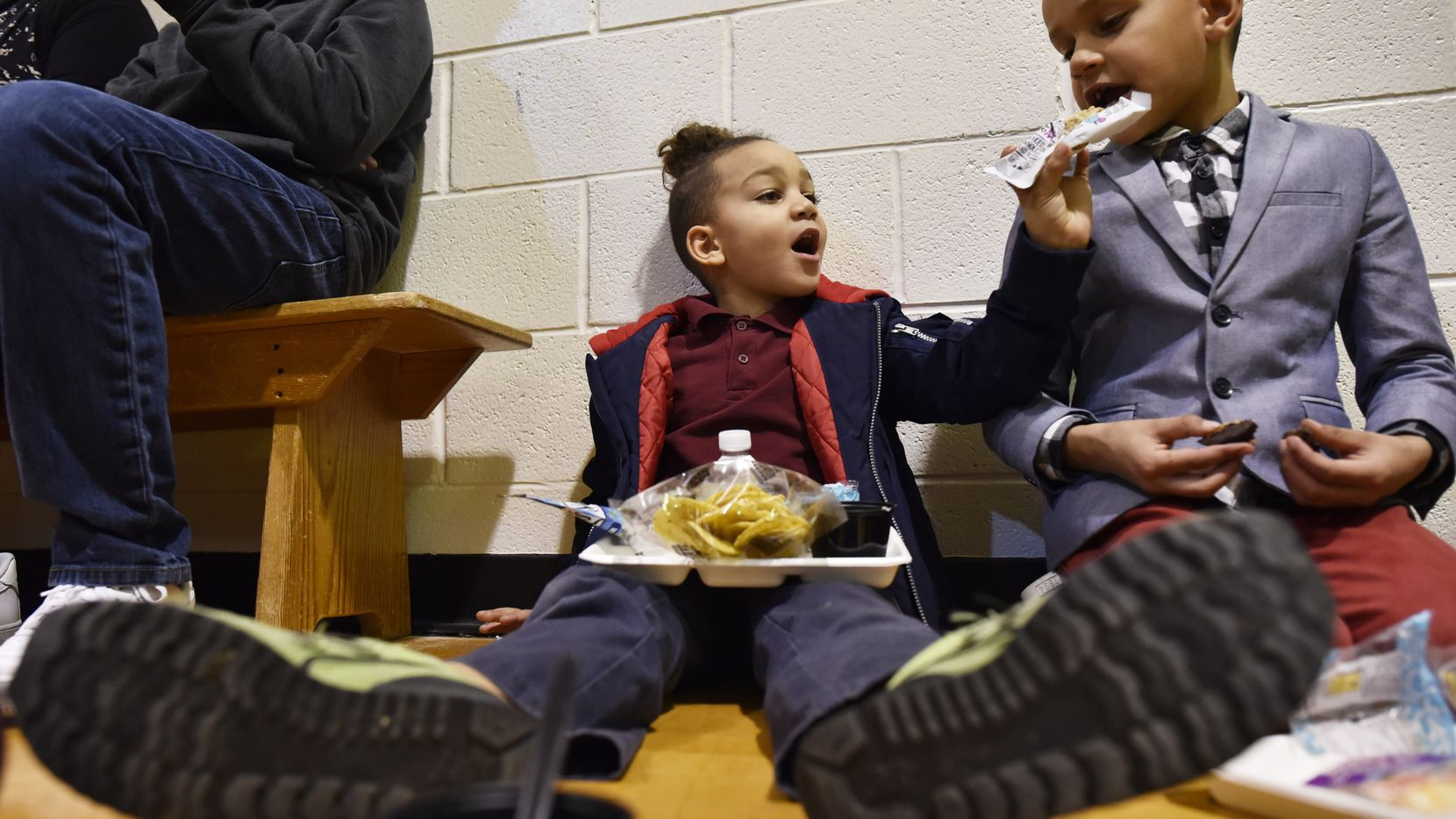 Elon Mitchell, left, tries to feed his brother Maxwell Mitchell a snack as the family taste tested potential offerings for school lunch Harry Stone Montessori Academy. The Dallas school district hosted the event to gauge what kids will like better for next year's school menu.
