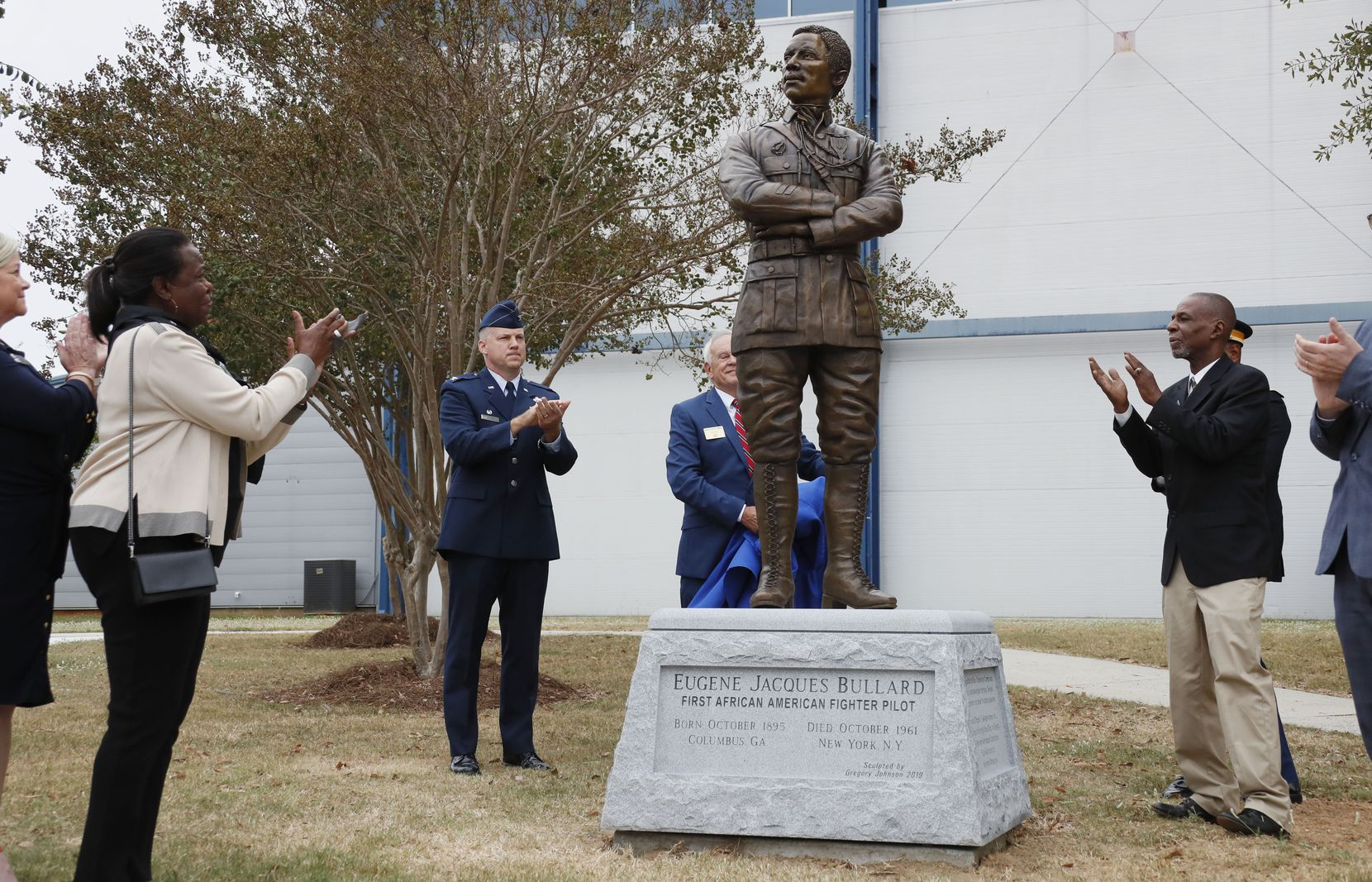 "Harriett Bullard White (far left) and William Bullard (far right)  join in applause  after the statue of Eugene Bullard was unveiled on Wednesday, Oct. 9, 2019, at the Museum of Aviation near Robins Air Force Base in Georgia.   Awarded France's Croix de Guerre for his heroism at the Battle of Verdun, Bullard joined France's air service, becoming the world's first African American fighter pilot and earning the nickname ""The Black Swallow of Death."" To honor him on his birthday in the state he fled more than a century ago, Georgia's WWI Centennial Commission will unveil a statue of Bullard."