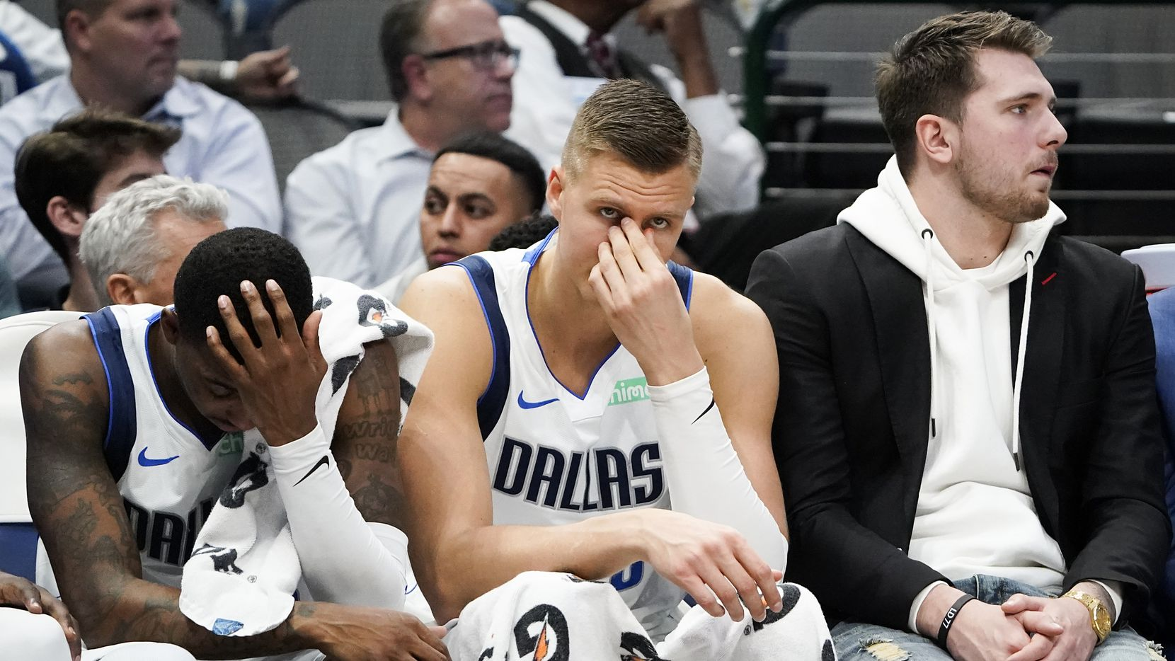 Injured Dallas Mavericks guard Luka Doncic (right) sits on the bench with forward Kristaps Porzingis (center) and guard Delon Wright (left) during the second half of an NBA basketball game against the Memphis Grizzlies at American Airlines Center on Wednesday, Feb. 5, 2020, in Dallas.
