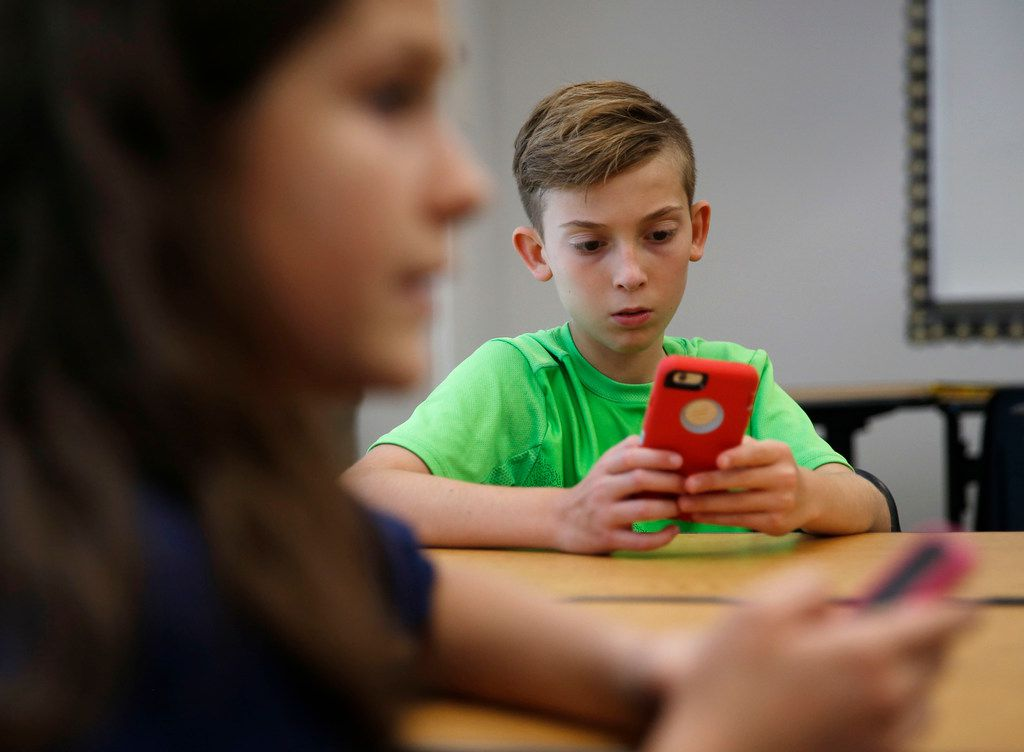 "Sixth-graders Brock Benner (right), 11, and Lauren Bazan (foreground left), 11, look for the STOP!t app. Frisco ISD is also launching a new campaign called ""Your Words Matter"" to educate students about the consequences of what they say or post online."