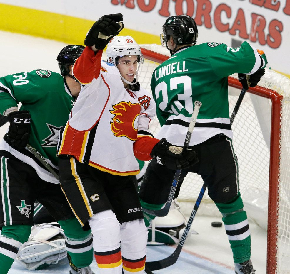 Calgary Flames center Sean Monahan (23) reacts after scoring a goal against Dallas Stars defenders Cody Eakin (20), Esa Lindell (23) and goalie Kari Lehtonen (32) during the third period of an NHL hockey game in Dallas, Tuesday, Dec. 6, 2016. The Flames won 2-1. (AP Photo/LM Otero)