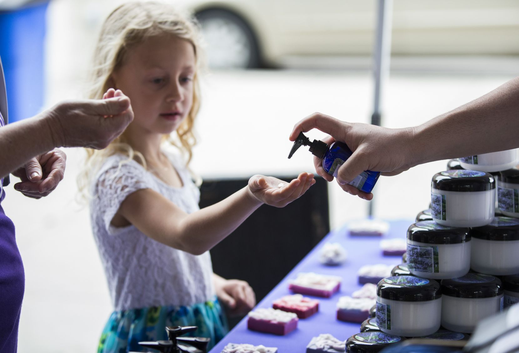 Visitors try out home made hand sanitizer from Musgrove Family Farm at the Dallas Farmers Market on Saturday, March 14, 2020.