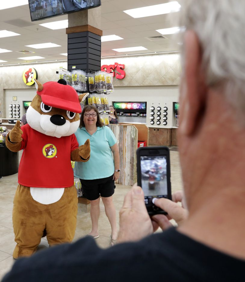 The Buc-ee's beaver mascot, left, poses with Dianna Bridgins as Michael Bridgins takes a photo at the new Buc-ee's in Melissa, TX, on Apr. 29, 2019.