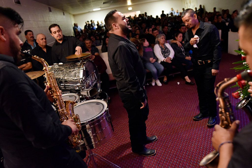 The band Lobillos Musical de Durango performs a song during a casket viewing for their former band mate Raul Ortega Cabrera at the funeral home.