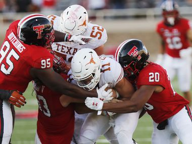 FILE - Texas Tech defensive lineman Jaylon Hutchings and linebacker Kosi Eldridge tackle Texas quarterback Sam Ehlinger during the second half of a game on Saturday, Sept. 26, 2020, in Lubbock. (AP Photo/Mark Rogers)