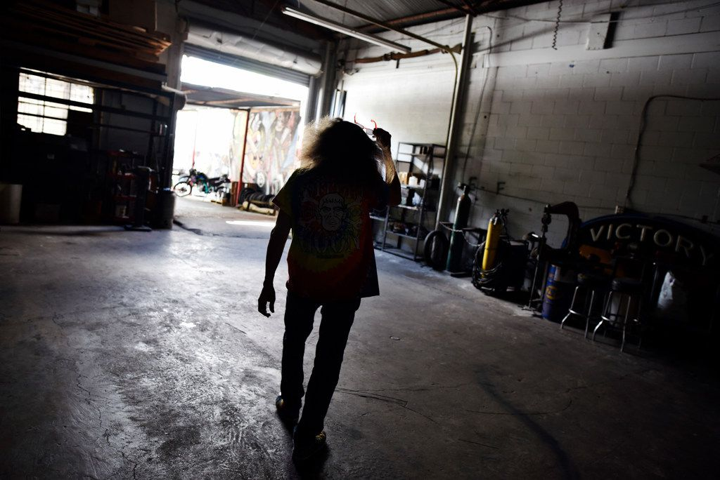 Owner Rick Fairless walks outside of his garage to the concert and patio areas of Strokers Dallas.