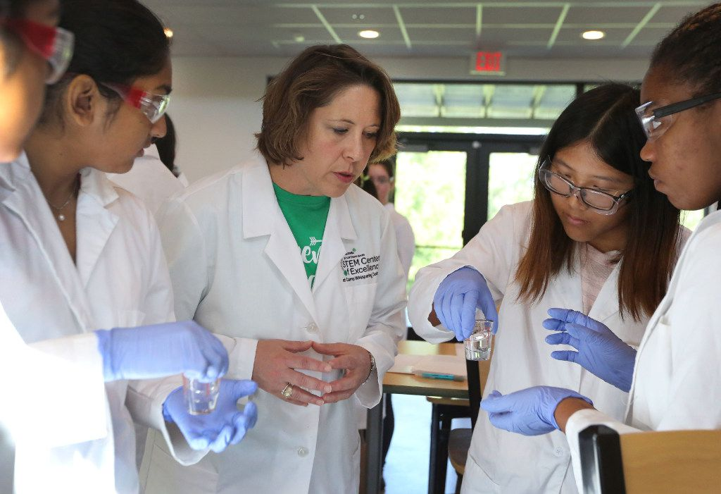 Northeast Texas Girl Scouts CEO Jennifer K. Bartkowski (center) watches as high school-age girls gain hands-on experience in pharmaceutical discovery and development  during a class at the Girl Scout summer camp at Camp Whispering Cedars in Dallas.